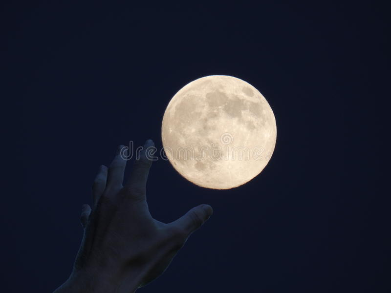`Earth Is Not Enough` - Greedy Hand of a Man. Hand reaching for the Moon. Man want to possess it royalty free stock image