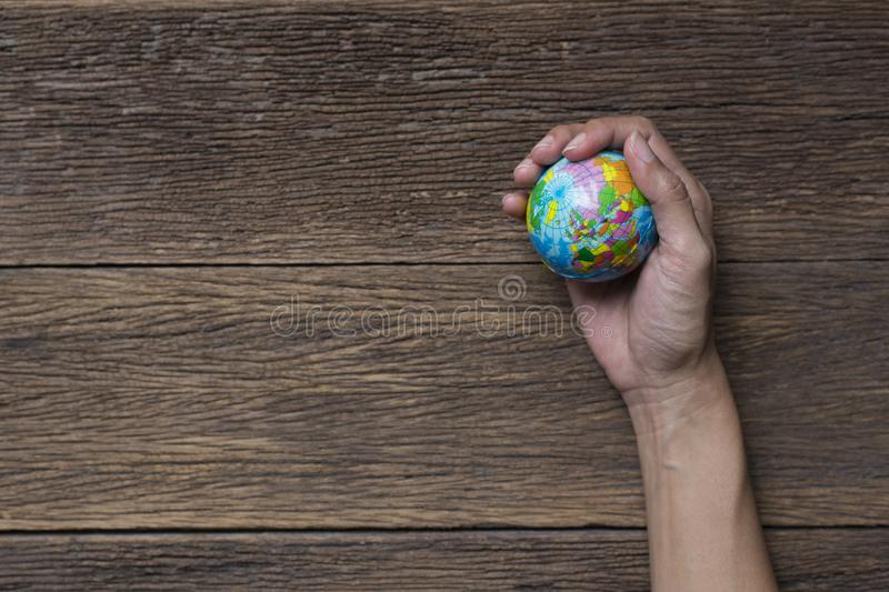 Earth planet in female hand on wood table royalty free stock photo