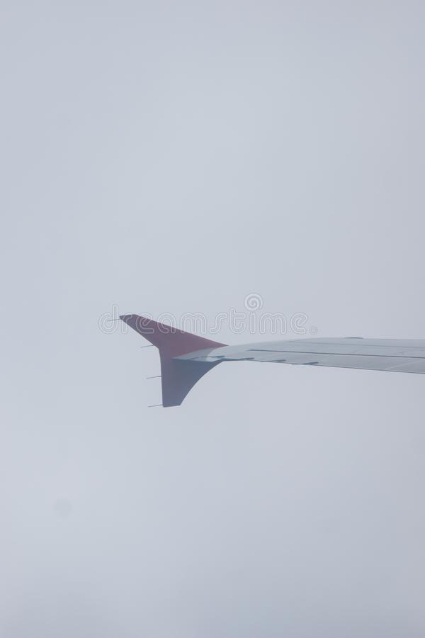 Earth in the porthole under the wing of an airplane. Flying in the fog above the clouds, nothing is visible stock photo
