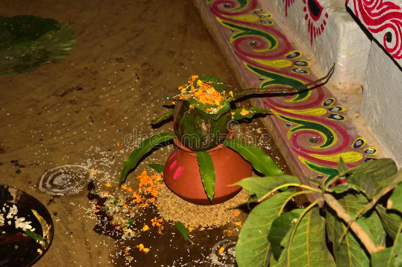 Earthen pot and mango leaves with floral decoration. A green coconut on a earthen pot and mango leaves with floral decoration. essential in hindu puja stock images