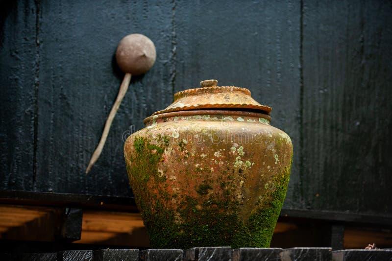 Earthenware bowl Parece viejo y tiene un fondo oscuro los asiáticos tienden a poner agua potable delante de la casa fotos de archivo