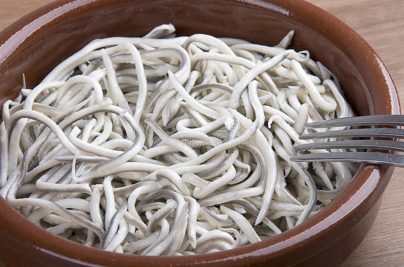 Earthenware bowl withyoung eels cooked with garlic stock photography