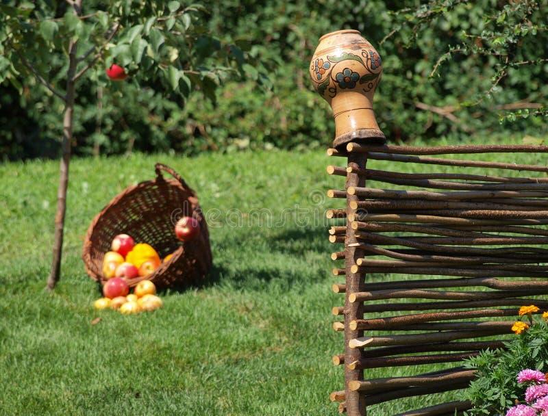Earthenware dzbanka obwieszenie na łozinowym ogrodzenia en tle zielona trawa i kosz jabłka zdjęcia stock
