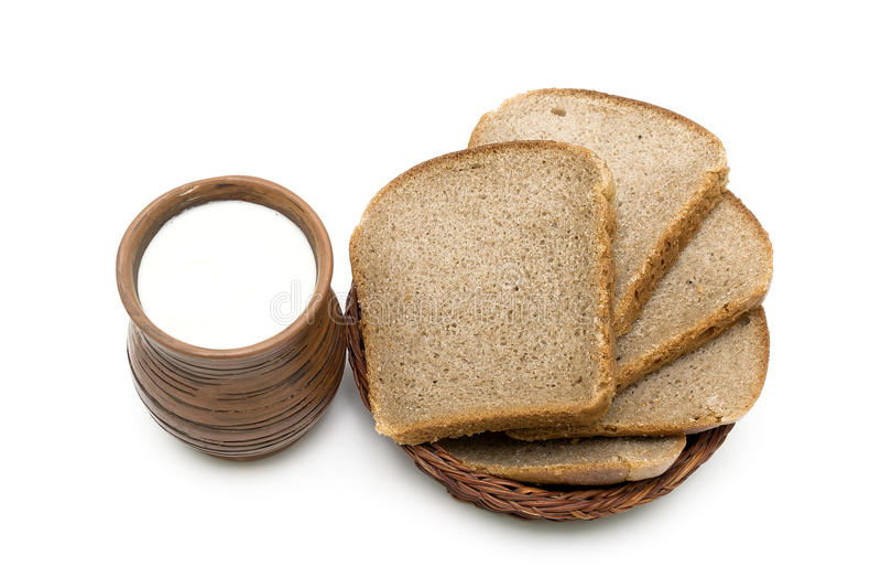 Earthenware kubek z mlekiem i chlebem na białym tle zdjęcie stock