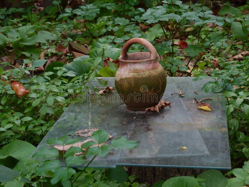 Earthenware pot in a garden stock image