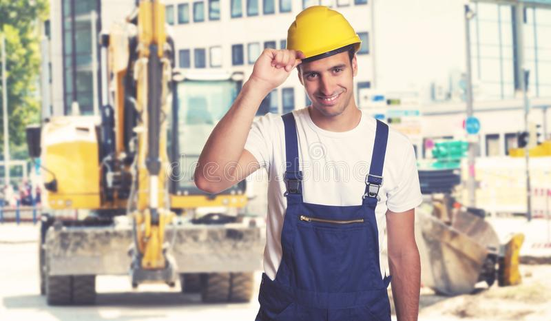 Earthmover with handsome latin american construction worker royalty free stock image