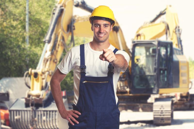 Earthmover with pointing latin american construction worker royalty free stock images