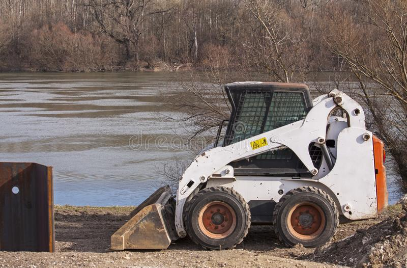 Earthmover on the protection dam under construction royalty free stock photo