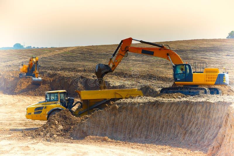 Earthmoveren laddar jordningen i lastbilen royaltyfri bild