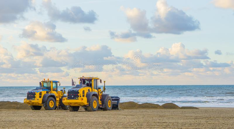 Earthmoving equipment machines working at the beach for maintenance moving sand industrial agriculture stock photos