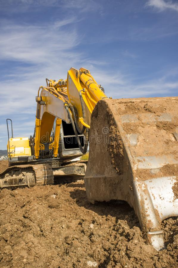 Earthmoving excavator preparing the construction site soil stock photos