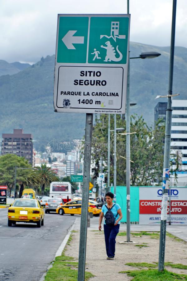 Earthquake evacuation sign in Quito. Earthquake evacuation sign with a godzilla sticker on it in Quito, Ecuador royalty free stock images