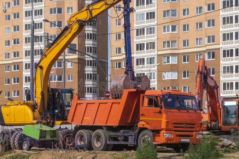 Earthworks. Industrial excavator loading earth into large truck vehicle. Repair point in front of apartment building. Earthworks. Industrial excavator loading royalty free stock image
