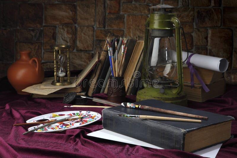 Easel με τις βούρτσες βρίσκεται στον πίνακα κοντά στην παλαιά ελαιολυχνία Τυποποιημένος ως αναδρομική ακόμα ζωή Εκλεκτική εστίαση στοκ φωτογραφία