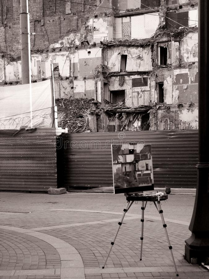 Easel on background of destroyed building. Artist decided to sketch demolished house. royalty free stock image