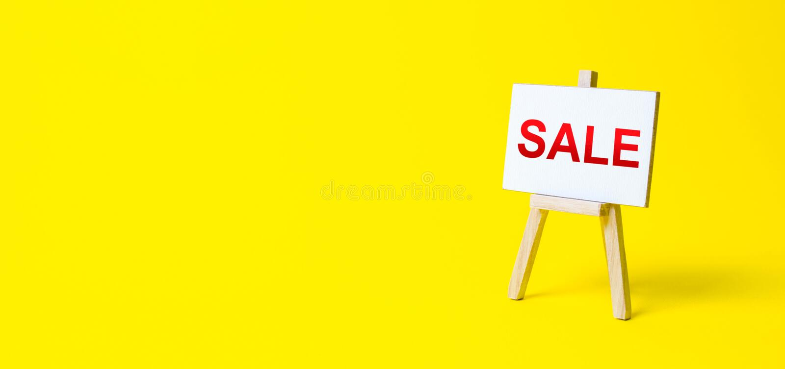 Easel sign with the words Sale. Advertising marketing. Discount. Shopping online. Increase sales and attract new customers. Sale of goods and products by stock photography