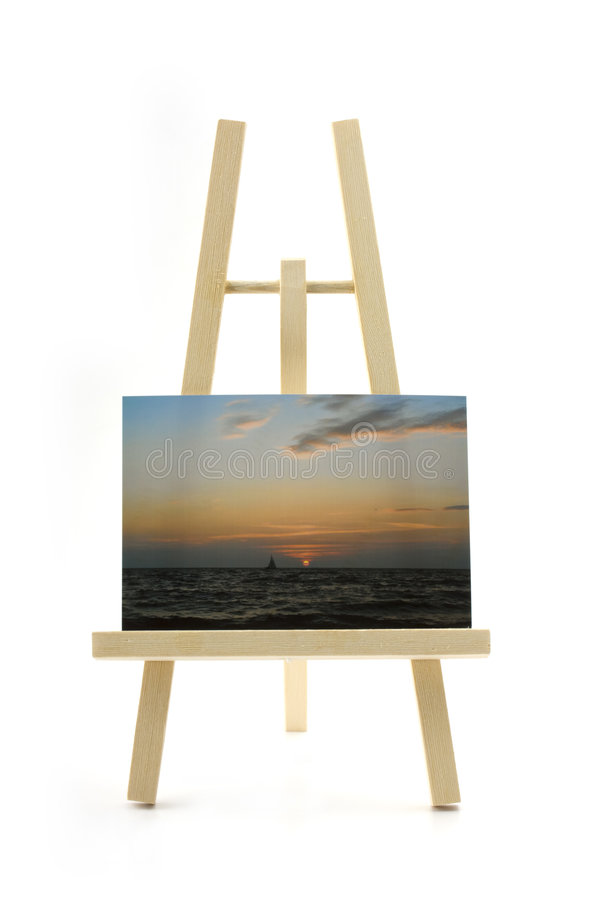 Easel with sunset photo. Wooden easel with sunset photo on white background stock images