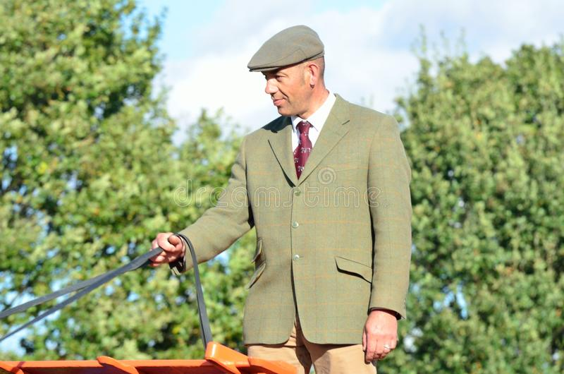 East Anglia Equestrian Fair English country gent holding reins of Carthorse. IPSWICH SUFFOLK UK 25 October 2014: East Anglia Equestrian Fair English country gent stock photos