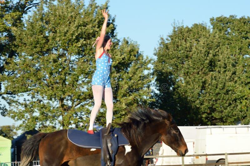 East Anglia Equestrian Fair girl standing on horseback waving to crowd. IPSWICH SUFFOLK UK 25 October 2014: East Anglia Equestrian Fair girl standing on stock photo