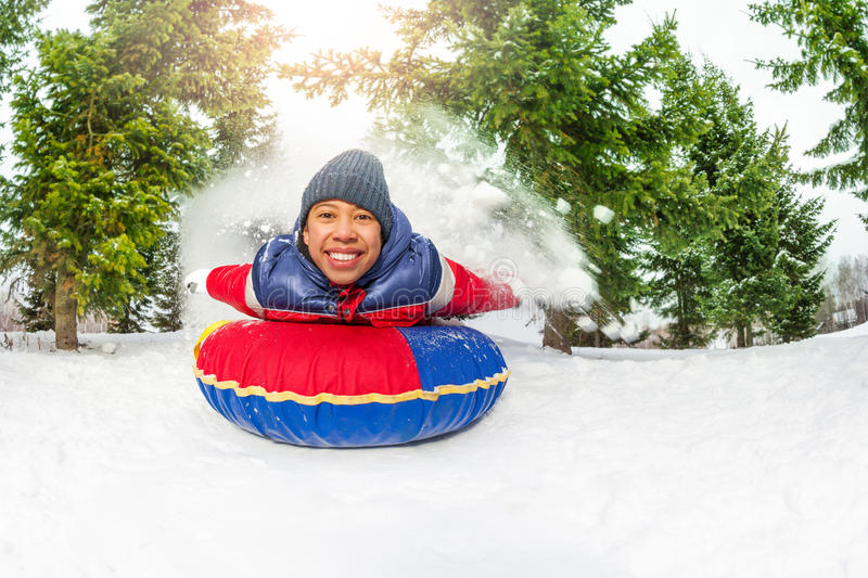 East Asian boy on snow tube in winter alone royalty free stock image
