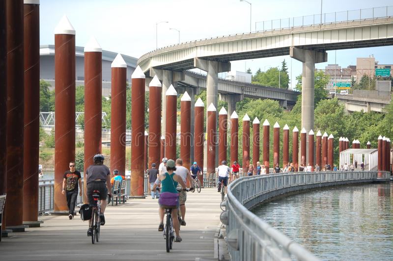 Cyclists and pedestrians on the East Bank Esplanade, Portland, OR. The East Bank Esplanade is a pedestrian and bicycle path along the east shore of the royalty free stock photo