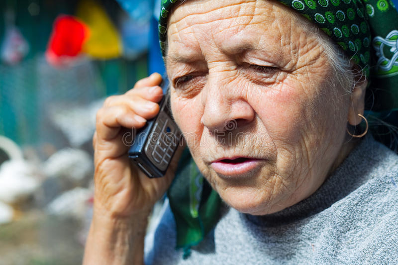 East european senior woman and mobile phone stock photography