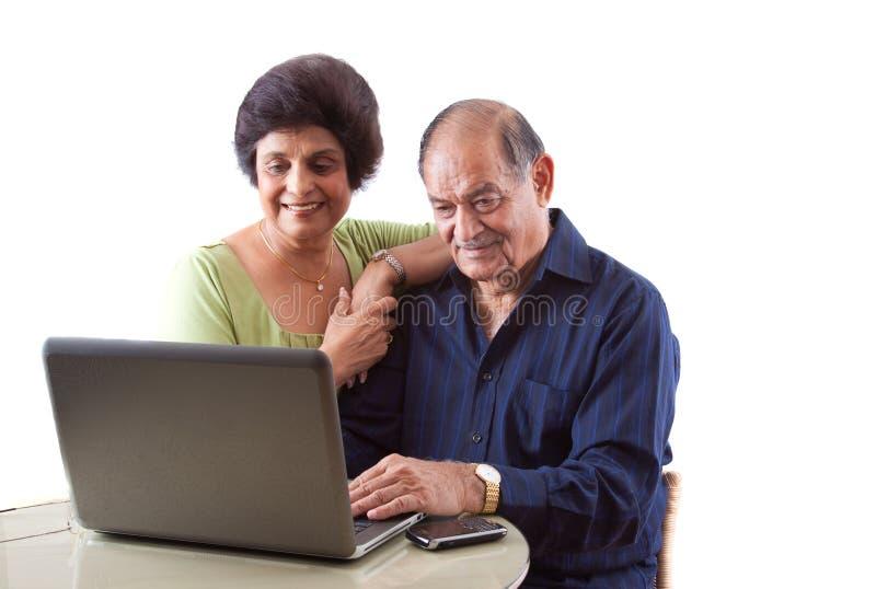 East Indian Elderly Couple on Computer. Portrait of a smiling elderly East Indian couple on computer laptop stock image