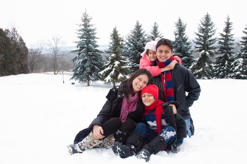 East Indian family playing in the snow. A beautiful East Indian parents play with her children in the snow royalty free stock photos