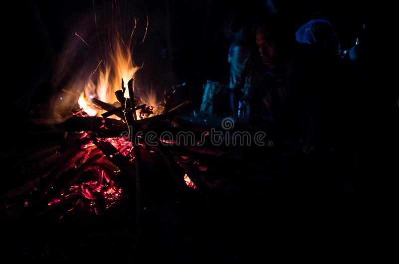 EAST JAVA, INDONESIA JANUARY 2017: Indonesian man sitting in front of camp fire after surf session. With people in the background stock photography