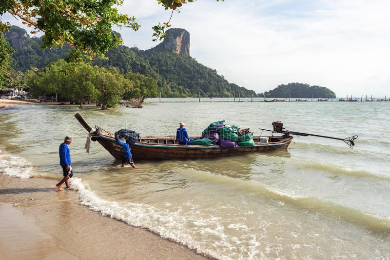 The hotel staff unloads from the Thai long-tail boat Luggage on the. East Railay, Krabi Province, Thailand - January 18, 2019: The hotel staff unloads from the stock images