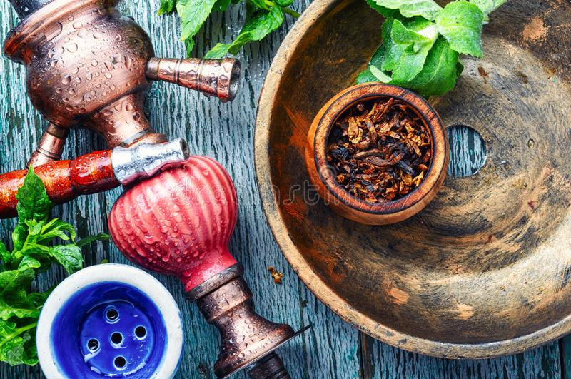 Smoking hookah with mint. East smoking hookah with mint flavor.Shisha mint tobacco.Shisha hookah with spearmint royalty free stock photography