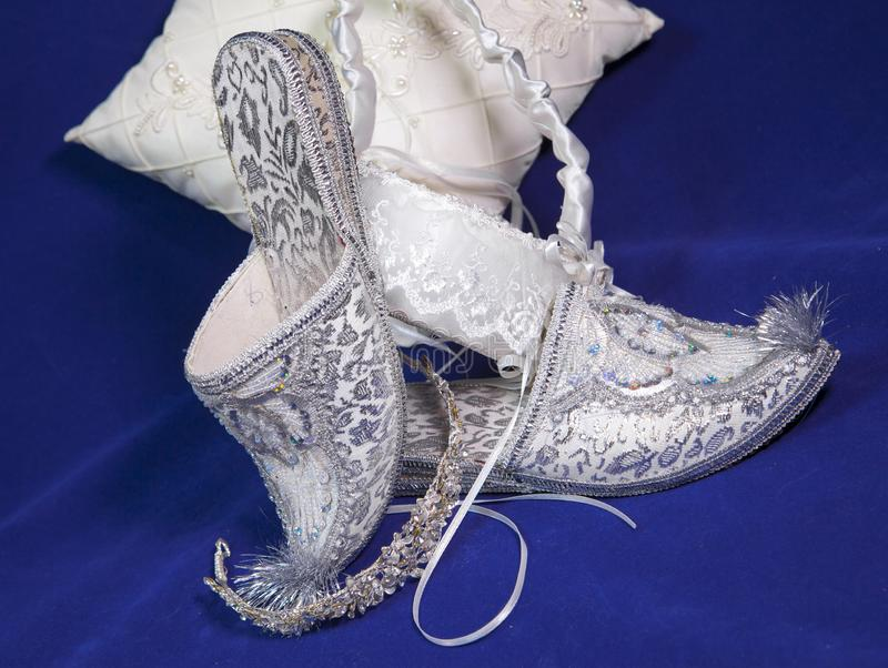 East style bride wedding shoes on a blue velvet stock photos