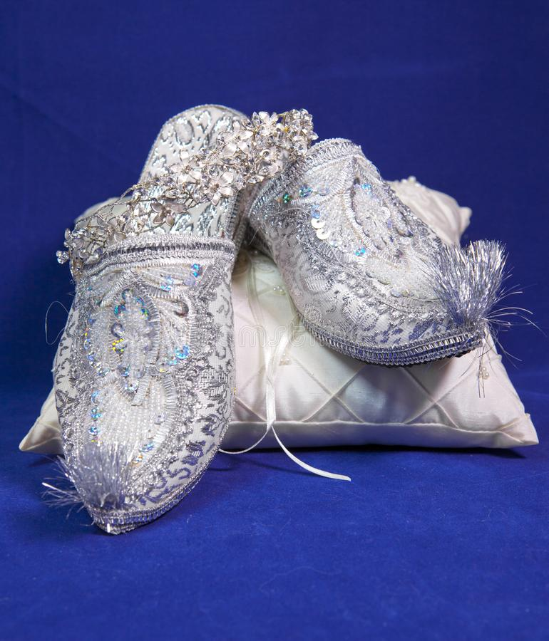 East style bride wedding shoes on a blue velvet stock image