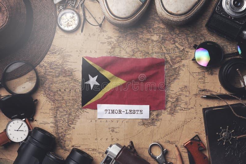 East Timor Flag Between Traveler`s Accessories on Old Vintage Map. Overhead Shot.  stock image