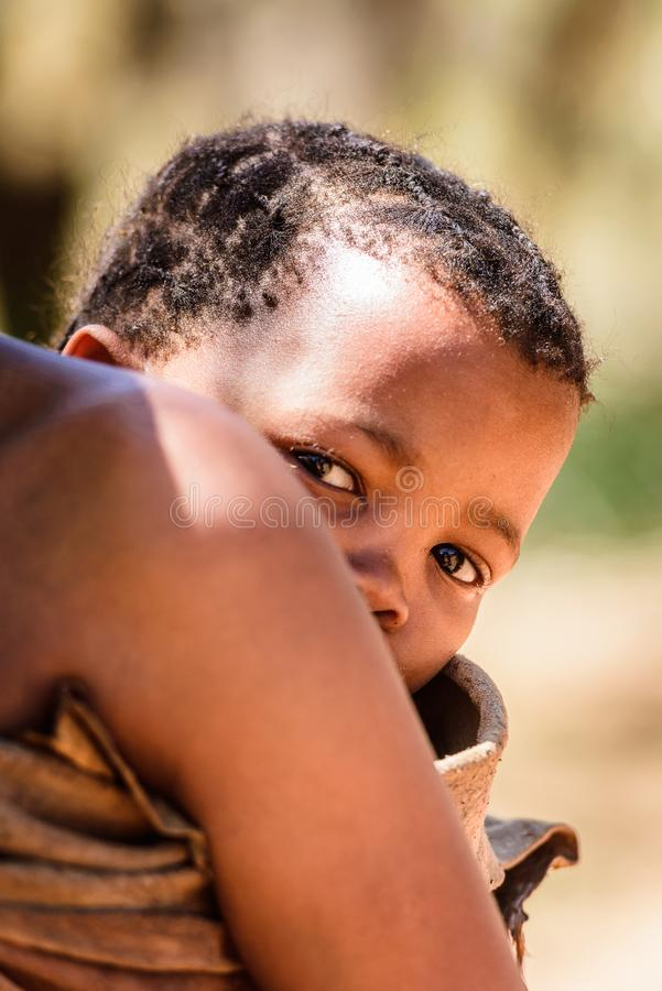 Bushman people in Namibia. EAST OF WINDHOEK, NAMIBIA - JAN 3, 2016: Unidentified bushman baby on his mother back. Bushman people are members of indigenous hunter royalty free stock photo