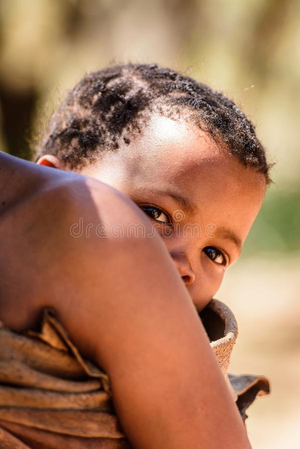 Bushman people in Namibia. EAST OF WINDHOEK, NAMIBIA - JAN 3, 2016: Unidentified bushman baby on his mother back. Bushman people are members of indigenous hunter royalty free stock photos