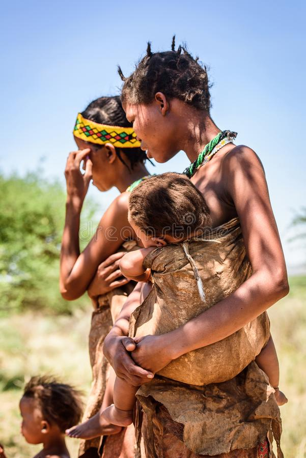 Bushman people in Namibia. EAST OF WINDHOEK, NAMIBIA - JAN 3, 2016: Unidentified bushman family. Bushman people are members of various indigenous hunter-gatherer stock photo