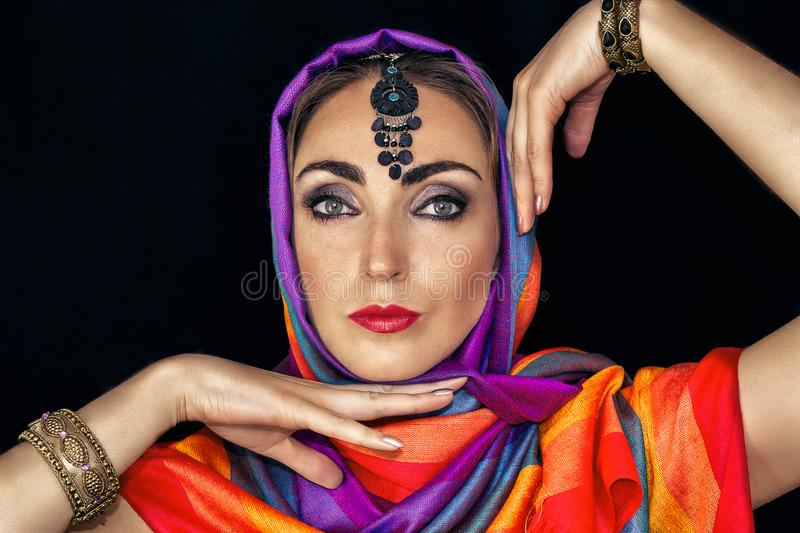 East woman in burqa with jewels on a black background stock image