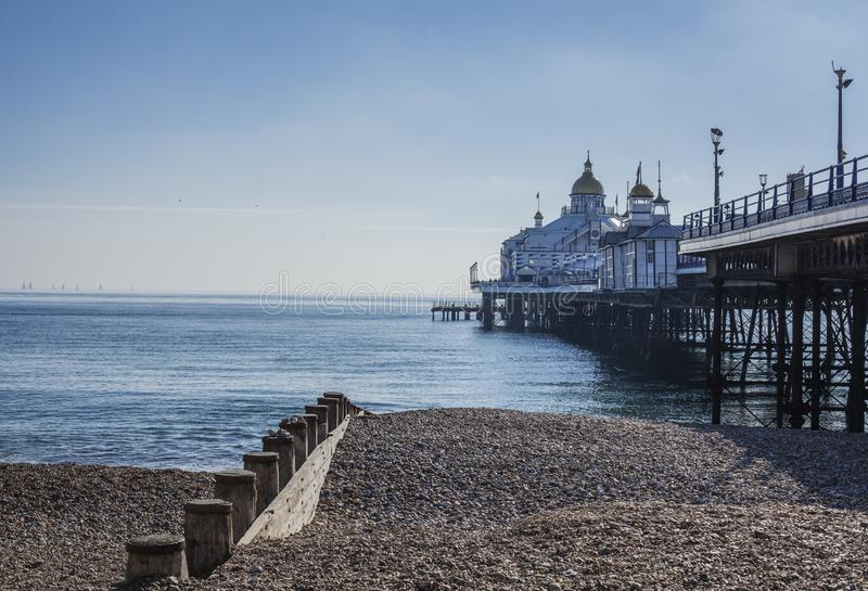 Eastbourne, East Sussex, England - the pier and blue waters of the sea. This image shows a view of the pier and the blue waters of the sea in Eastbourne, East royalty free stock photography