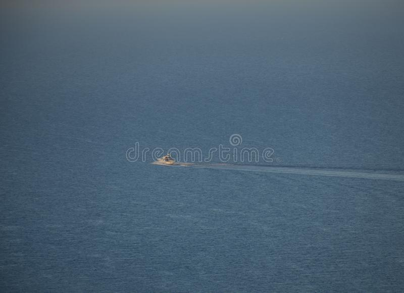 Eastbourne, East Sussex, England - the view a boat sailing across blue seas. This image shows a view of cliffs in Eastbourne, East Sussex, England, the UK. It stock photography
