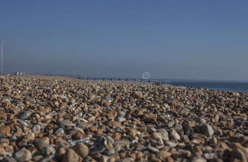 Eastbourne, East Sussex - pebbles on the beach and blue skies. This image shows a view of a beach and some blue skies in Eastbourne, East Sussex. It was taken royalty free stock image