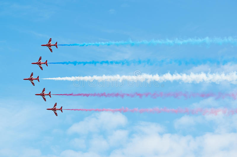 EASTBOURNE, ENGLAND - AUGUST 14, 2015: RAF aerobatic team The Red Arrows perform at the Airbourne airshow.The smoke trails left by royalty free stock image