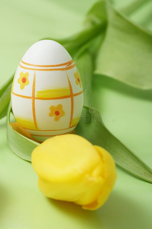 Easter. Egg with yellow tulip on green background stock photo