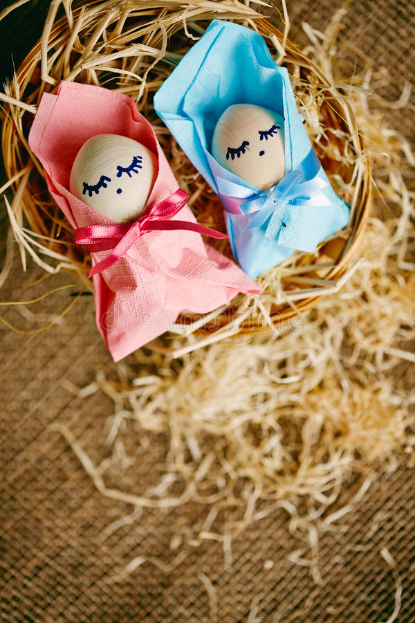 Easter babies. Image of two baby Easter eggs wrapped into pink and blue paper royalty free stock image