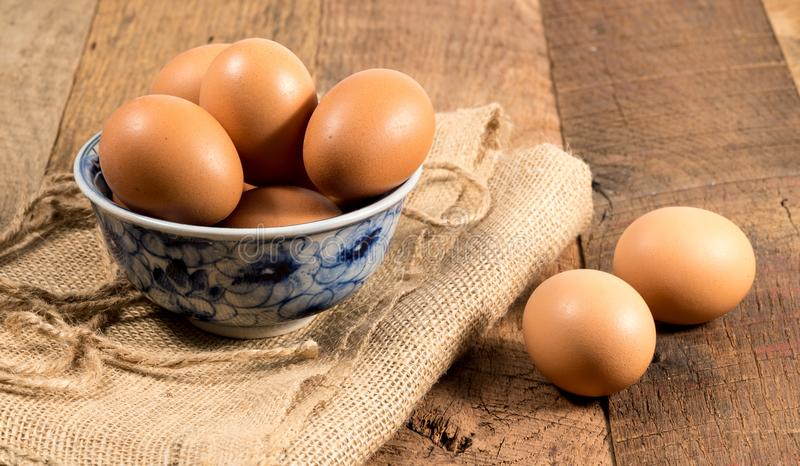 Freshly laid organic eggs in bowl on wooden bench. Easter background with brown organic eggs arranged in a bowl on burlap sack on rustic wooden table stock image
