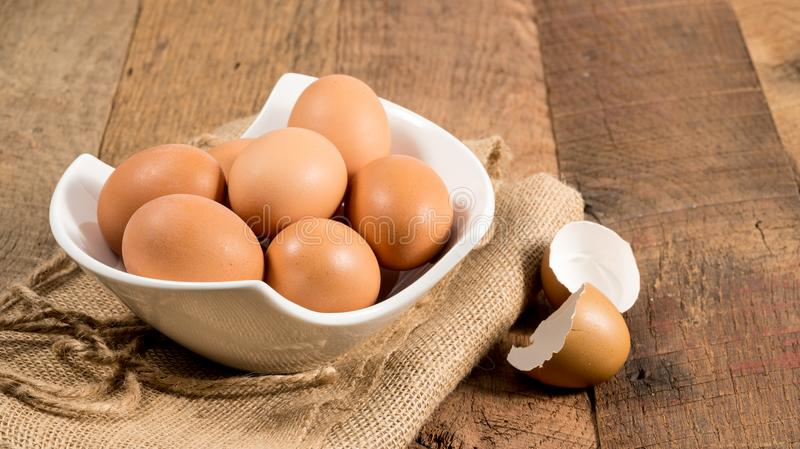 Freshly laid organic eggs in bowl on wooden bench. Easter background with brown organic eggs arranged in a bowl on burlap sack on rustic wooden table royalty free stock image