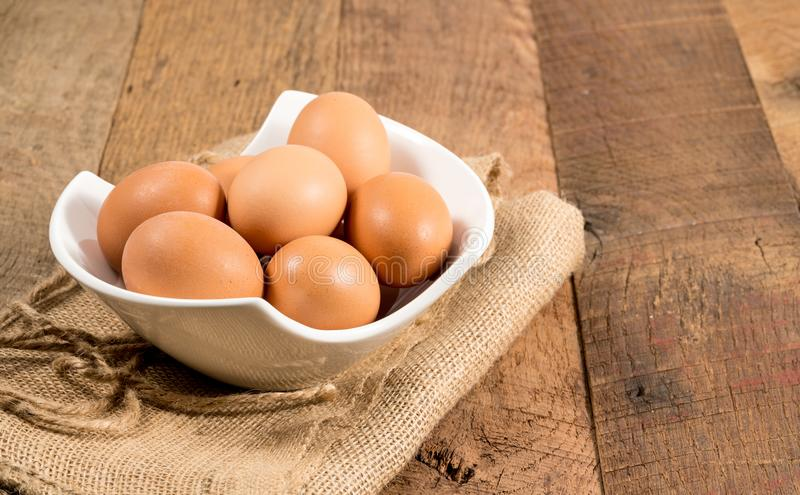 Freshly laid organic eggs in bowl on wooden bench. Easter background with brown organic eggs arranged in a bowl on burlap sack on rustic wooden table stock photo