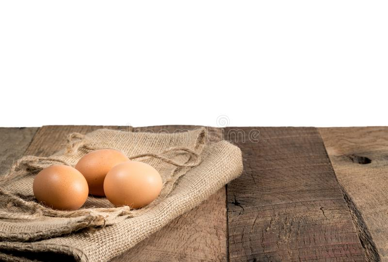 Freshly laid organic eggs on wooden bench. Easter background with brown organic eggs arranged on burlap sack on rustic wooden table with background royalty free stock photos