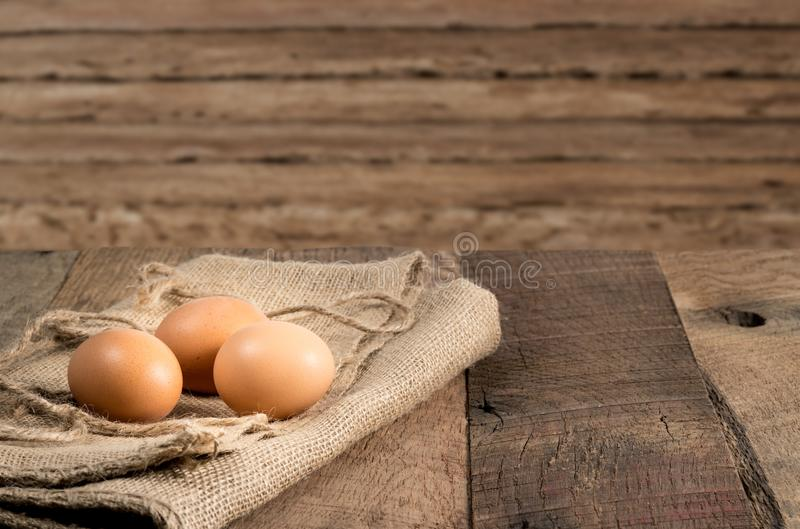 Freshly laid organic eggs on wooden bench. Easter background with brown organic eggs arranged on burlap sack on rustic wooden table stock image