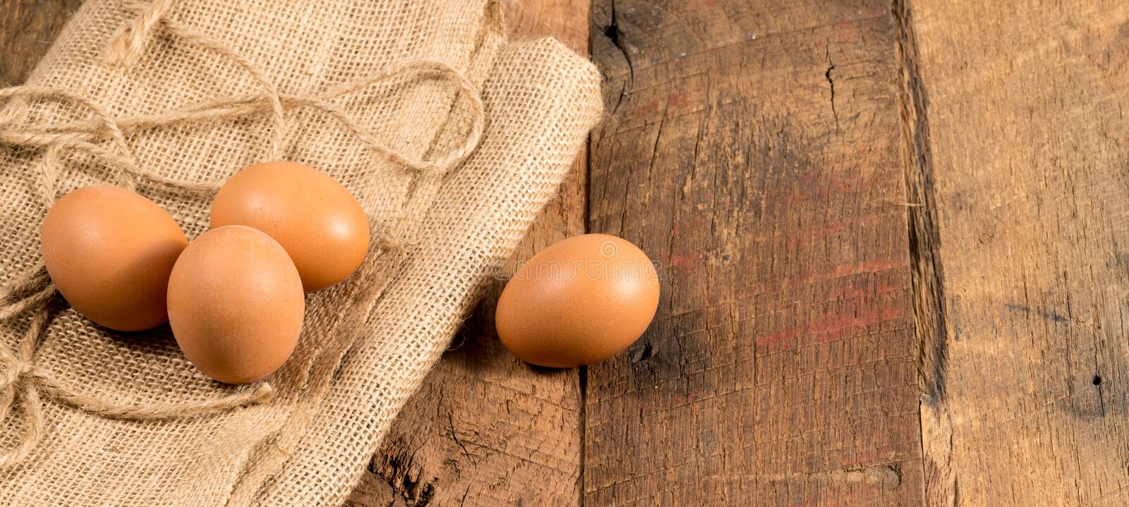 Freshly laid organic eggs on wooden bench. Easter background with brown organic eggs arranged on burlap sack on rustic wooden table stock photo
